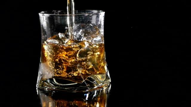 vídeos de stock e filmes b-roll de uísque de ser vertido para um vidro contra fundo preto.  fechar - rum bebida branca