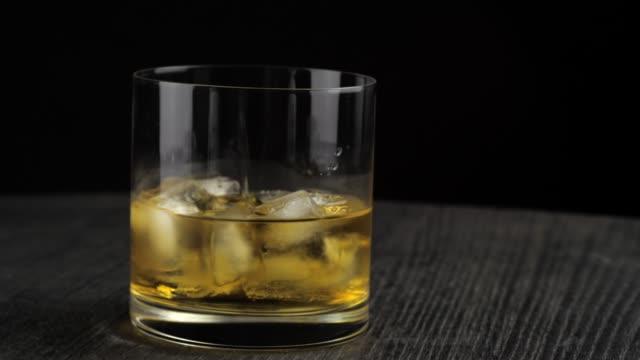 uísque é derramado em um copo com gelo - vídeo