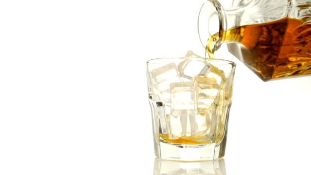 Whiskey on the rocks poured from a rystal decanter on white backround with copy space video