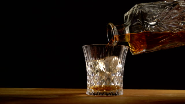 whiskey on the rocks poured from a сrystal decanter - decanter video stock e b–roll