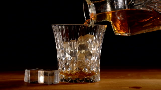 whiskey on the rocks poured from a rystal decanter - decanter video stock e b–roll