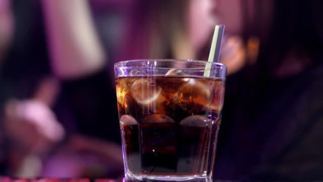whiskey oder cognac in ein glas mit eiswürfeln am tresen vor einem unscharfen hintergrund - turngerät mit holm stock-videos und b-roll-filmmaterial