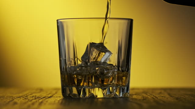 whiskey poured in glass at yellow background. glass of whisky with ice cubes - scotch whisky video stock e b–roll
