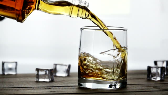 whiskey pouring into a glass with ice cubes on old wooden table in slow motion - rum superalcolico video stock e b–roll