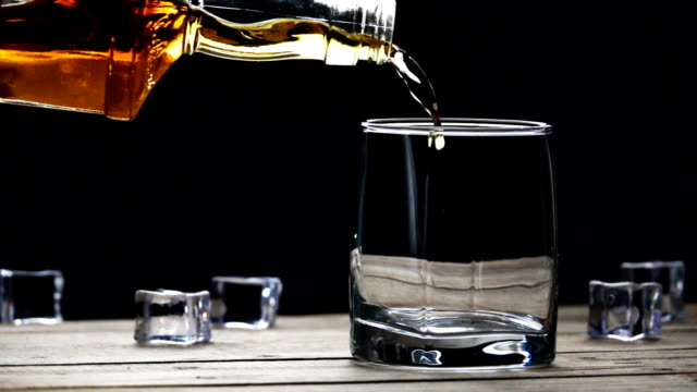 whiskey pouring into a glass with ice cubes on old wooden table in slow motion - whisky video stock e b–roll