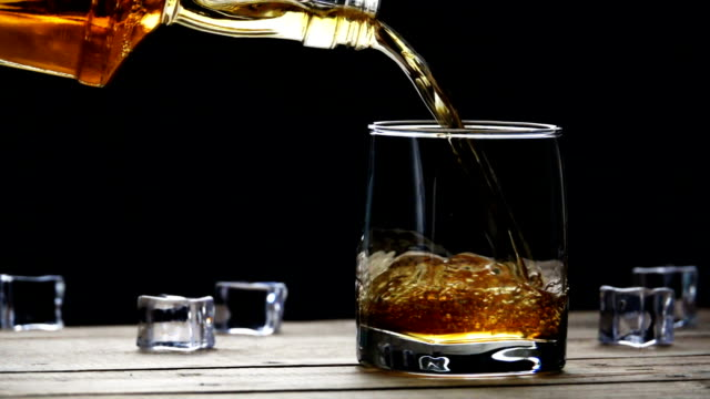 whiskey pouring into a glass with ice cubes on old wooden table in slow motion. seamless cinemagraph video - whisky video stock e b–roll