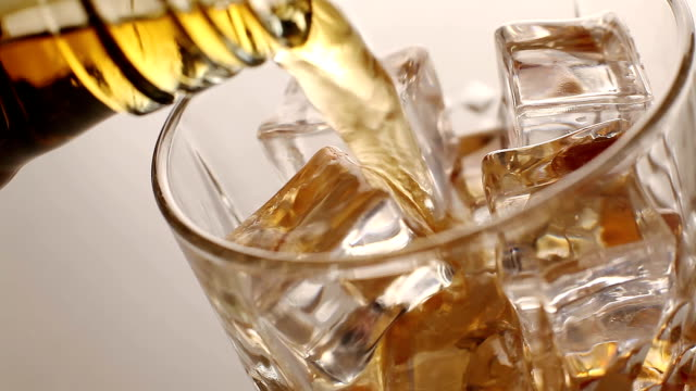 Whiskey pours into a glass with ice cubes video
