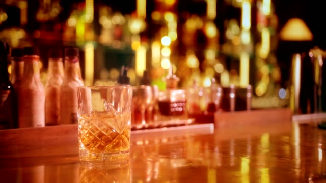 whiskey with ice served in retro glass on bar counter - scotch whisky video stock e b–roll