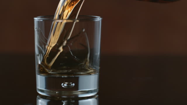 whisky poured into glass in slow motion - whisky video stock e b–roll