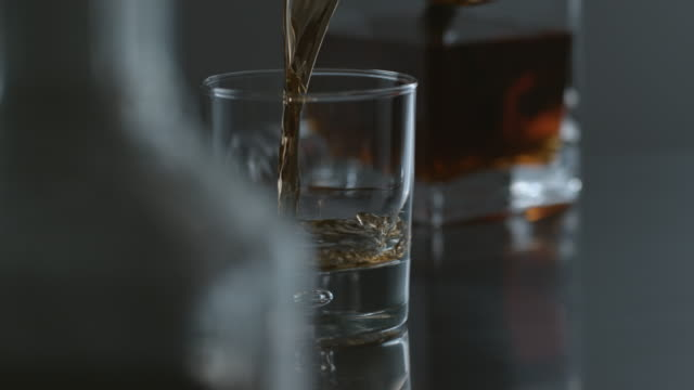 whisky poured into glass in slow motion - scotch whisky video stock e b–roll