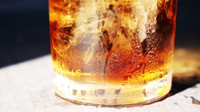 vídeos de stock, filmes e b-roll de whisky com gelo em um copo - tea drinks