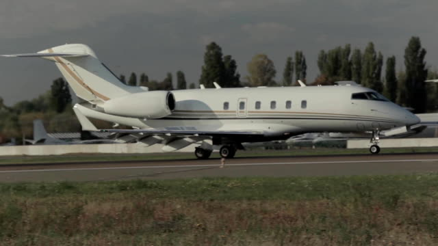 White airplane landed in the airport The airplane is landing in the airport. Passanger airplane is going to go down in the airport. The aircraft in the international airport. The airplane is moving on the runway. military private stock videos & royalty-free footage