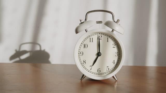 vit väckarklocka är placerad på ett träbord och ljuset lyser genom gardinerna på morgonen. - alarm clock bildbanksvideor och videomaterial från bakom kulisserna