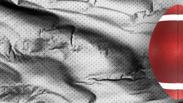 white american football jersey textured with a football on a vertical view - trykot filmów i materiałów b-roll