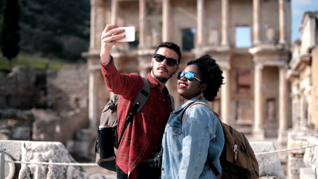 White and African couple taking a selfie in front of the celcus library. video