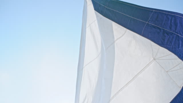 4K White and blue sailboat sail blowing in wind against sunny blue sky, real time 4K White and blue sailboat sail blowing in wind against sunny blue sky, real time. MS, pan down, tilt up, zoom out, shaky, real time. yachting stock videos & royalty-free footage