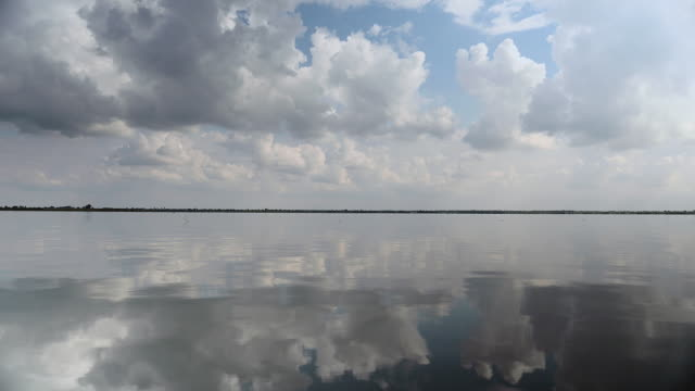 White and grey clouds in blue sky reflected in lake water