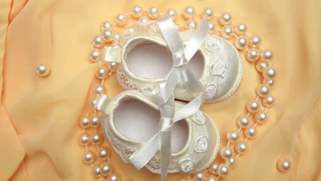 White baby booties with string of pearls White baby booties with string of pearls on revolving yellow blanket baby booties stock videos & royalty-free footage