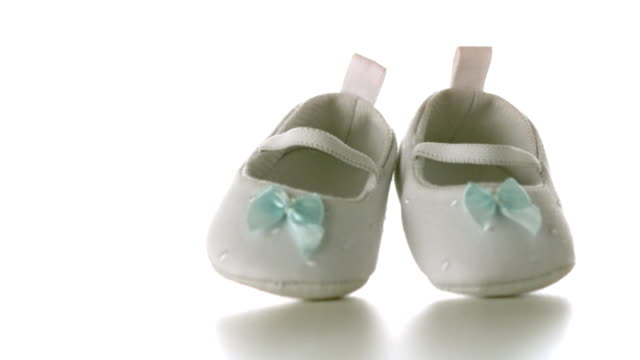 White baby shoes falling on white surface White baby shoes falling on white surface in slow motion baby booties stock videos & royalty-free footage
