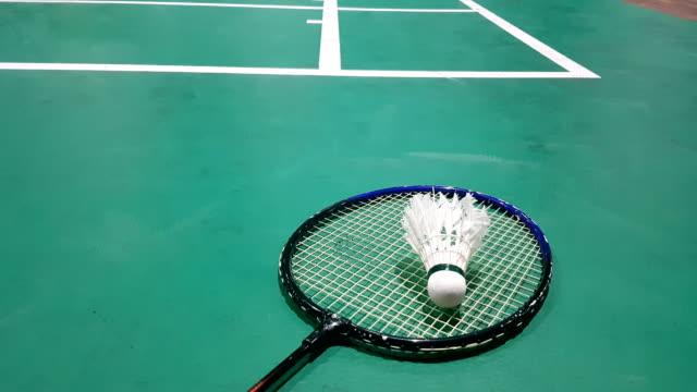 weißer badminton-shuttlecock auf einem grünen boden mit verschwommenen spielern auf badminton court - badminton stock-videos und b-roll-filmmaterial