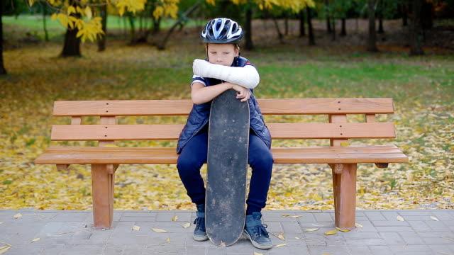 white boy with broken arm sitting with skate - wine filmów i materiałów b-roll