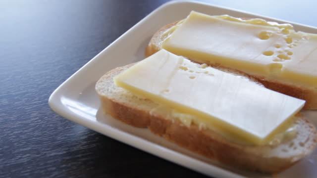 2 vita bröd smörgåsar med smör och ost på en tallrik. kameran rör sig runt detta till höger. - cheese sandwich bildbanksvideor och videomaterial från bakom kulisserna