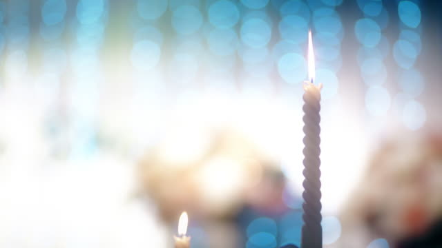 white candles with retro candlestick holder indoors against illuminated bokeh background. - candeliere video stock e b–roll