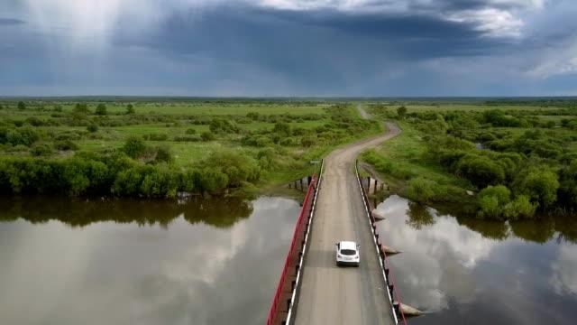 vidéos et rushes de la voiture blanche conduit le long du pont au-dessus de la vue aérienne calme de fleuve - voiture blanche