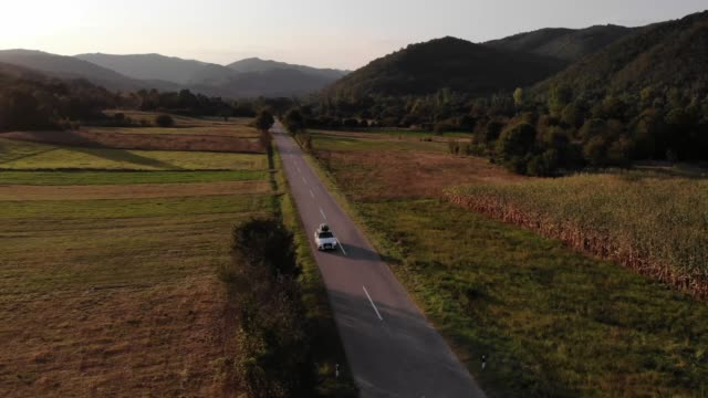 A white car drives down an empty country road at a golden summer sunset