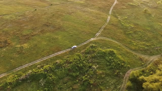 White car on scenic unpaved road with fork aerial tracking shot on sunset White car on scenic unpaved road with fork aerial tracking shot on sunset high angle in summer fork stock videos & royalty-free footage