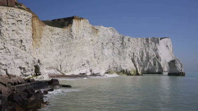 White chalk cliffs Seaford East Sussex England UK near Seven Sisters with waves lapping cliffs and blue sea and sky video