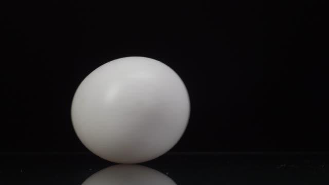 stockvideo's en b-roll-footage met het witte kippenei dat en op een zwarte achtergrond met mooie bezinning draait. close-up - ei