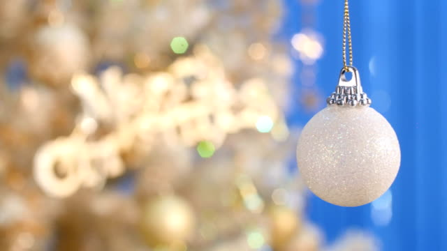 White Christmas Ball Ornament Close - up. White ornament ball turning in front of Christmas tree. christmas ornament stock videos & royalty-free footage
