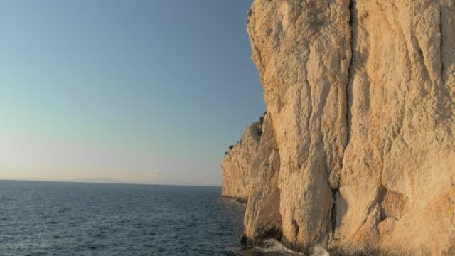vídeos de stock, filmes e b-roll de aerial precipício branco brilhando no sol acima do mar - penedo