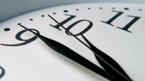 vit urtavla med tre långa svarta pilar som pekar femton minuter till tio - dag bildbanksvideor och videomaterial från bakom kulisserna