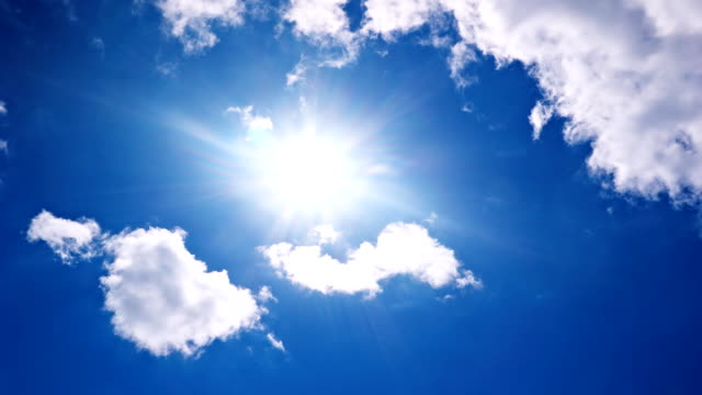White clouds flying on blue sky with sun rays time-lapse video