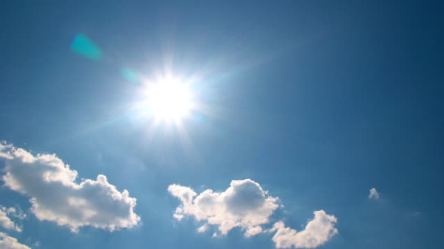 White clouds flying on blue sky with sun rays