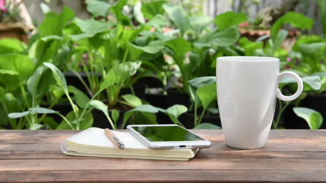 White coffee cup, mobile phone and notebook on wood table in green outdoor garden, morning time