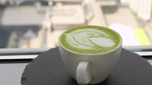 weiße kaffeetasse mit grüner matcha latte kunst rotiert auf einem steinplatte seitenansicht. vorlage für sommergetränkemenü von café und restaurant - milchkaffee stock-videos und b-roll-filmmaterial