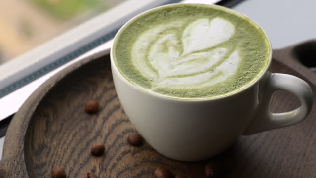 white coffee cup with green matcha latte art rotating on a stone plate side view. template for summer drink menu of cafe and restaurant