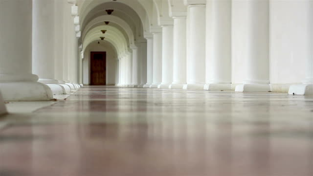 White Corridor with Arches Low angle shot of a white corridor with pillars and arches through which one person is walking. architectural column stock videos & royalty-free footage
