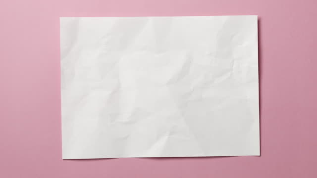 White crumpled paper texture on light blue or pink background. Stop motion animation.