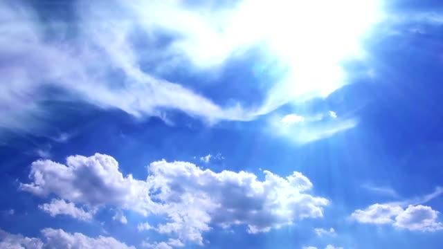 White cumulus and cirrostratus clouds in sun beam