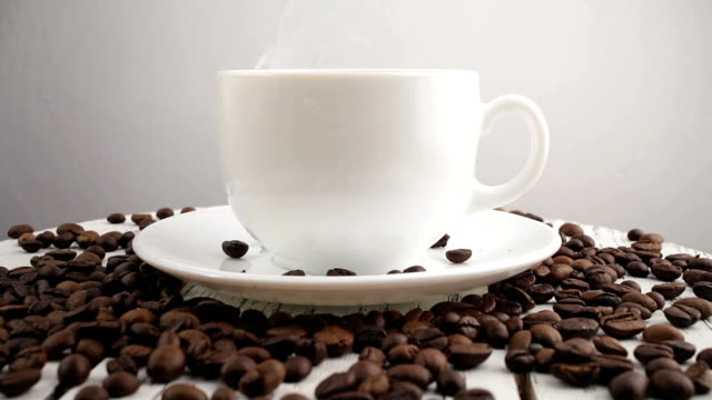 White cup with black, hot coffee standing on brown, roasted beans on sacking video