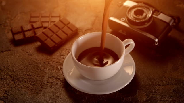 white cup with chocolate bar and retro camera on texture table - theobroma video stock e b–roll