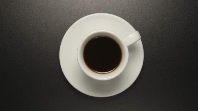 kaffeepause: weiße tasse mit kaffee trinken dreht sich am schwarzen tisch (stop-motion) - kaffeetasse stock-videos und b-roll-filmmaterial
