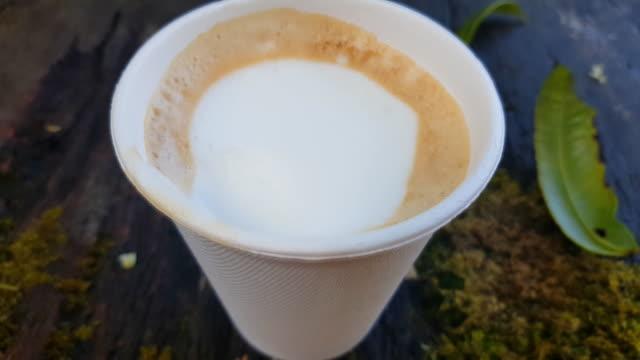日当たりの良い森の緑の苔の木のテーブルの上にコーヒーラテとホワイトカップ。 ビデオ