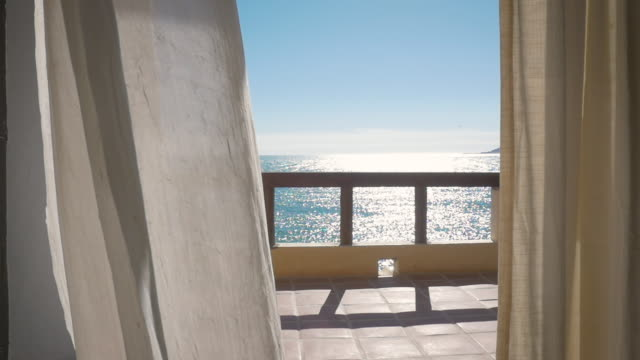 White Curtains Blow in Slow Motion on the Balcony of an Oceanfront Resort Hotel
