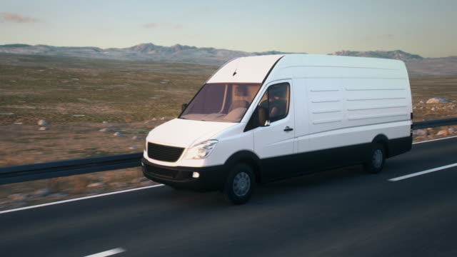 white delivery van driving along a desert road into the sunset - furgone video stock e b–roll