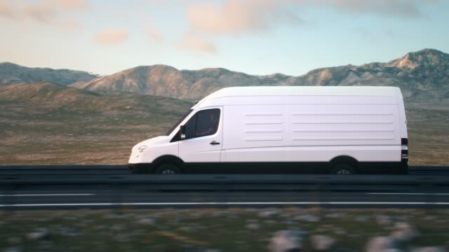 white delivery van driving along a desert road into the sunset